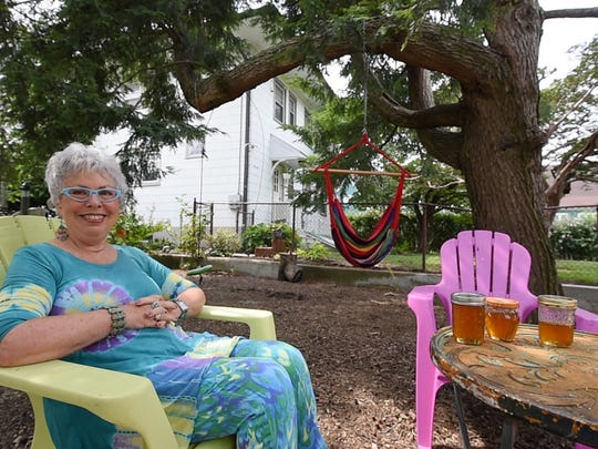 Susan Craver displays three jars of honey she extracted from honey comb that fell out of her backyard tree during a storm. The tree broke off near the top, revealing a large bee hive now protected with a cover resembling a pizza box.