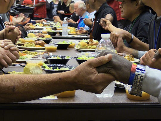 Patrons of the Phoenix Rescue Mission say grace before eating a meal.