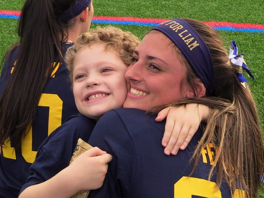 Liam Craane hugs John Jay's Paige Fetzer prior to game against Roy C. Ketcham at John Jay High School in Wiccopee on Wednesday. Liam Craane is a 6-year-old battling cancer, whom the John Jay team adopted as a teammate last year.