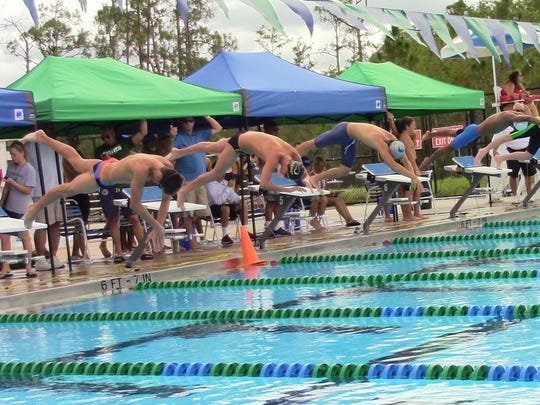 Participants in the boys' 400 freestyle relay dive off the blocks during Wednesday's District 1A-9 Championships at the FGCU Aquatic Center