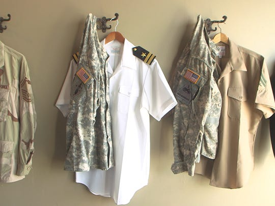 Service uniforms hang on the walls of Backward Flag