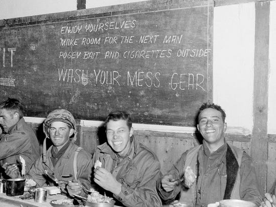 Members of a rifle team of the Second Battalion, Fifth Marine Regiment, dig in at Thanksgiving dinner in a mess hall in Chosin Reservoir, North Korea, Nov. 23, 1950. From left are: Cpl. James Balog, Pfc. Richard Dulac, and Nunzio Tonderella.