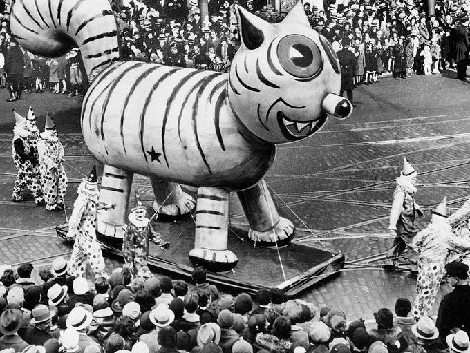 An outdoor float of a big cat makes its way down a