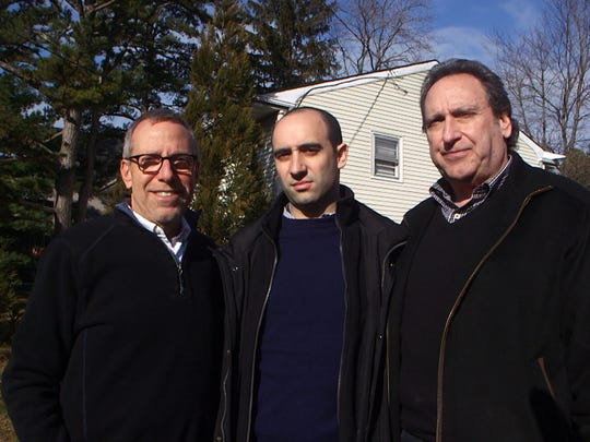 Brothers Harvey and David Sass pose with David's son Paul in front of the home where there father was murdered on 6/6/69.