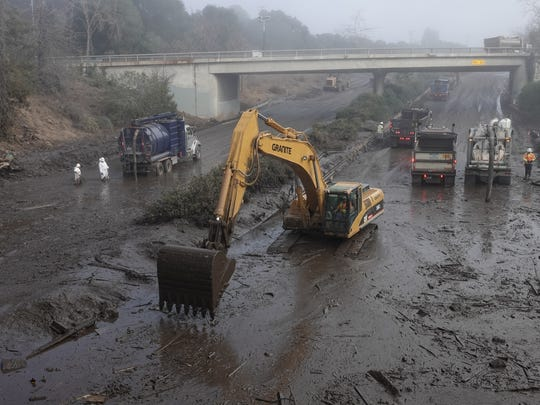 An excavator scoops slushy mud from southbound lanes of Highway 101 in Montecito Monday morning at the Olive Mill road overpass. It has been closed since Jan. 9, when heavy rains in the Thomas Fire burn area triggered deadly mud and debris flows in Montecito.