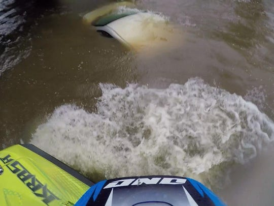 A submerged car can be seen from a Kalamazoo street