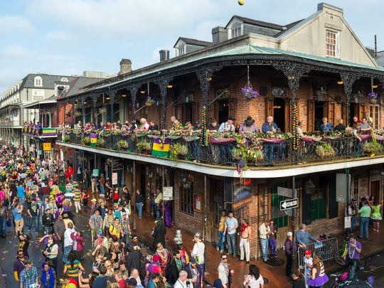 Visitors walk down New Orleans' Bourbon Street in this file photo. The Arkansas House recently approved a bill that would allow cities to designate 'entertainment districts' where patrons could drink outdoors, much like they can on Bourbon Street.