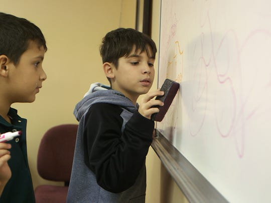 Gabriel, left, and Christyan, right, draw on a whiteboard