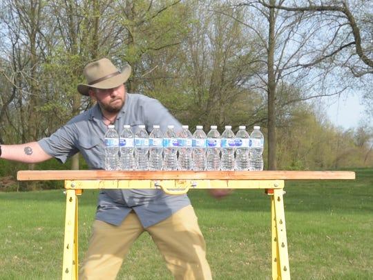 Dwayne Unger prepares to cut 11 water bottles in half