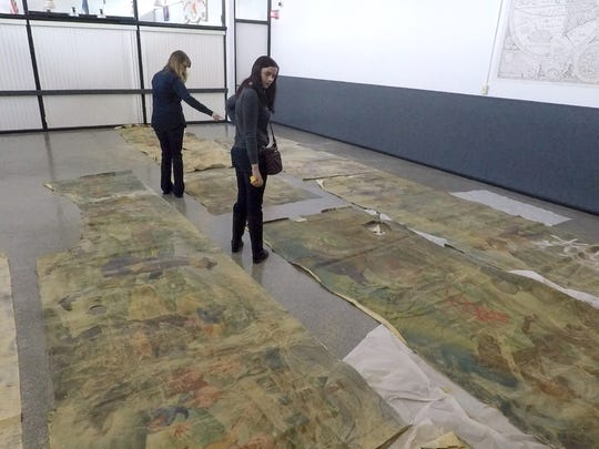 Elizabeth Skrabonja, left, and Colleen Moriarty of the Orangetown Historical Museum look over WPA murals that were recovered from the Rockland Psychiatric Center in Orangeburg May 7, 2018.