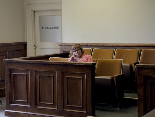 Lindy Lou Wells Isonhood sits in a jury box.