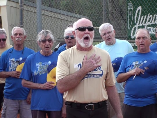 Everett Barber, age 69, leads softball players in singing