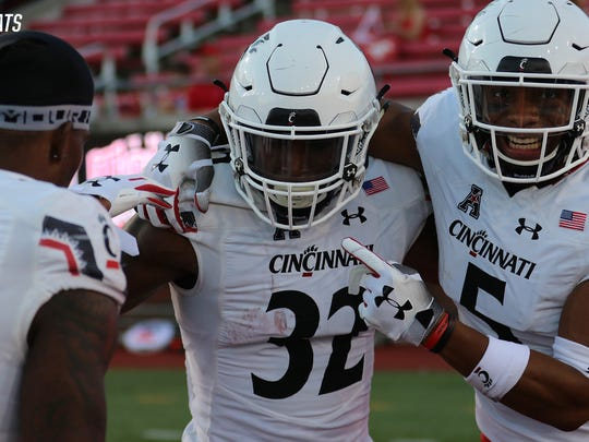 Cincinnati's James Wiggins (32) is congratulated by teammates Tyrell Gilbert and Darrick Forrest (5) after his 86-yard interception return won Saturday's game in overtime at SMU.