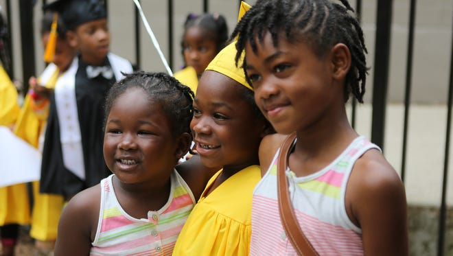Kindergartener Sadajisha Massey is photographed with her sister Shamyia, 4, and Kamyila, 8, after her kindergarten graduation at VLT Academy on Wednesday, May 28, 2014. The charter school in Pendleton closed in August. It's had academic and financial troubles through the years. The founders, a local couple, are devastated.