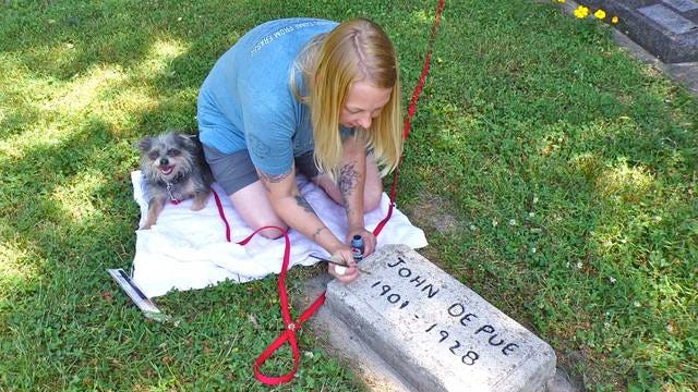 Amy Laube of Fraser is spearheading the cleaning efforts, which are all volunteer. Here, she paints the lettering of cement headstones to make them easier to read (with permission from the family). Photo by Sara Jordan-Heintz
