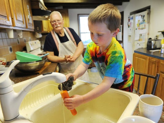 John McHenry, left, looks on as his 5-year-old grandson Keenan Lynch helps scrub carrots. Nutritionist Elisabeth D'Alto said involving your children in preparing there lunches is one way to get them to eat healthier. (Daily Record/Sunday News -- Jason Plotkin)