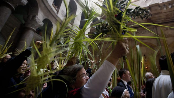 Christian pilgrims carry palm fronds at the Church of the Holy Sepulchre, traditionally believed by many Christians to be the site of the crucifixion and burial of Jesus Christ, in Jerusalem's old city, Sunday, April 14, 2019.