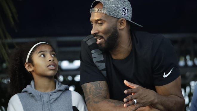 Former Los Angeles Laker Kobe Bryant and his daughter Gianna watch the U.S. national championships swimming meet in July 2018 in Irvine, California. Bryant, the 18-time NBA All-Star who won five championships and became one of the greatest basketball players of his generation during a 20-year career with the Los Angeles Lakers, died in a helicopter crash Sunday, Jan. 26, 2020. Gianna also died in the crash.