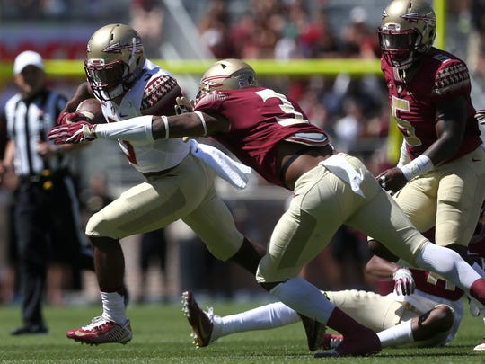 FSU's Cam Akers tries to break away from Derwin James during their Garnet and Gold spring game at Doak Campbell Stadium on Saturday, April 8, 2017.
