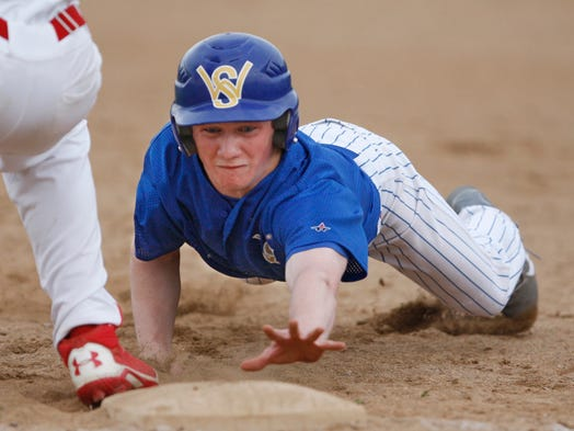 Webster Schroeder's Chris Young dives safely back to the first base ahead of the tag by Fairport's Jeff Waldrop in the third inning of their game at Fairport High.