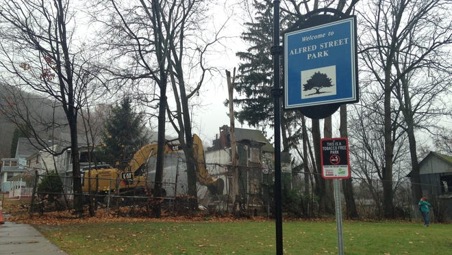 An excavator works at demolishing a house at 10 Alfred St. in Binghamton on Thursday. The city plans to incorporate the plot of land into the adjacent Alfred Street Park, Mayor Richard David said.