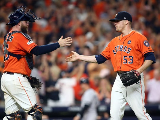 Houston Astros relief pitcher Ken Giles (53) and catcher Brian McCann (16) celebrate after beating the New York Yankees during game one of the 2017 ALCS playoff baseball series at Minute Maid Park on Friday, Oct. 13, 2017.