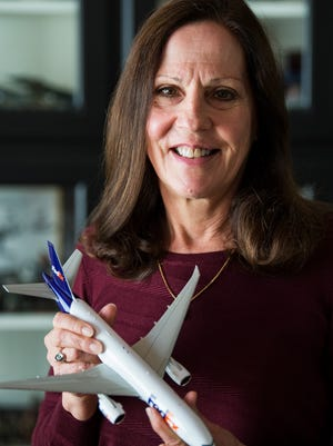 Jane Dyer holds a model of the airplane she pilots for FedEx in her Easley home on Tuesday, Oct. 24, 2017.