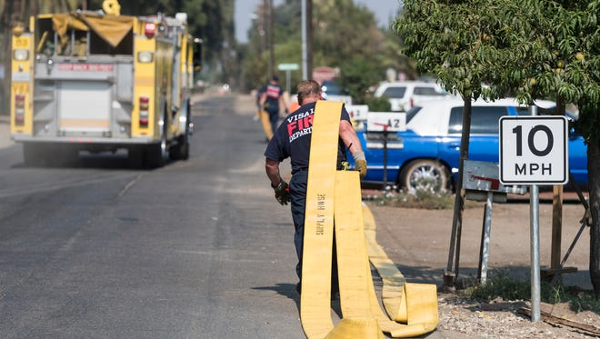 Visalia Fire Department picks up hose line after a mobile home fire south of Mooney Grove Park on Sunday, July 29, 2018.