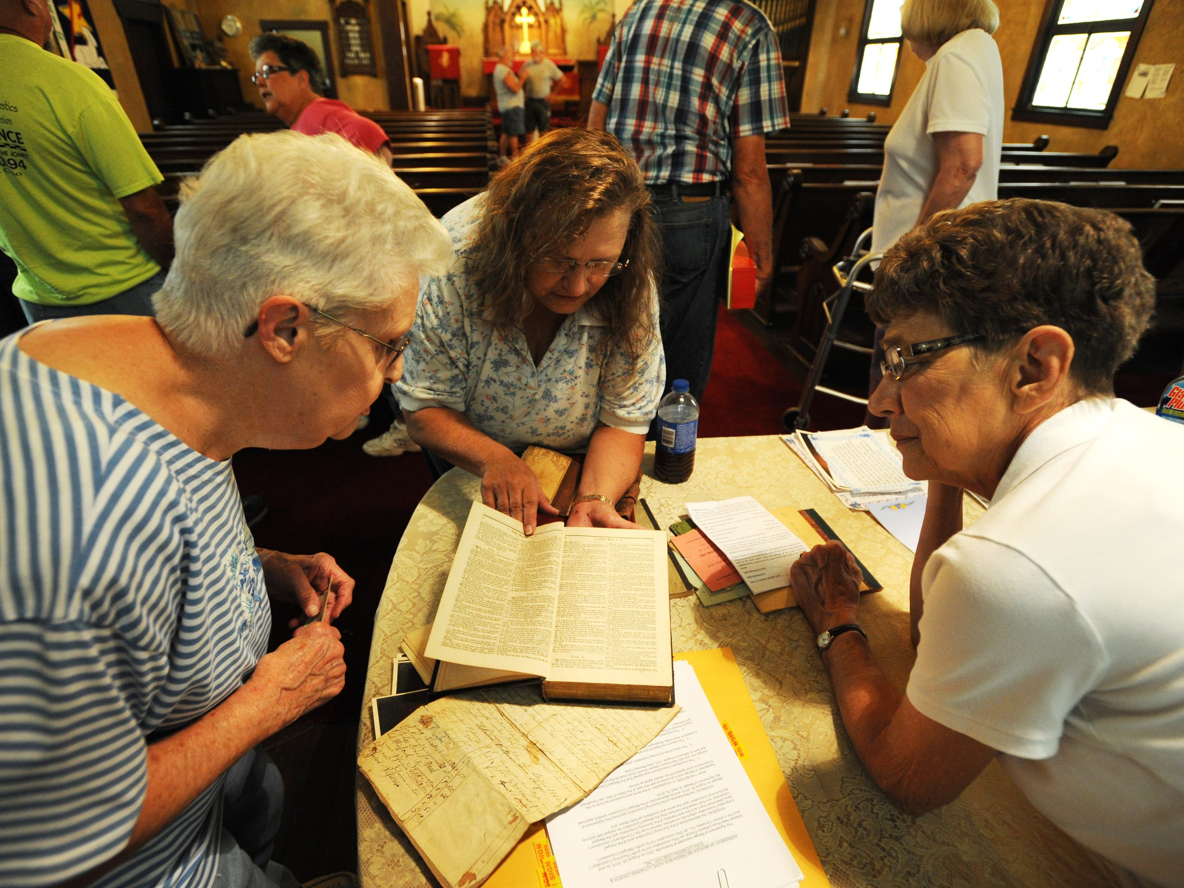 Willajene Vensel, left, Kaye Morgan and Pastor Mary Molnar look at a German bible found while cleaning out Zion Lutheran Church. Vensel is the longest-serving member of the congregation.