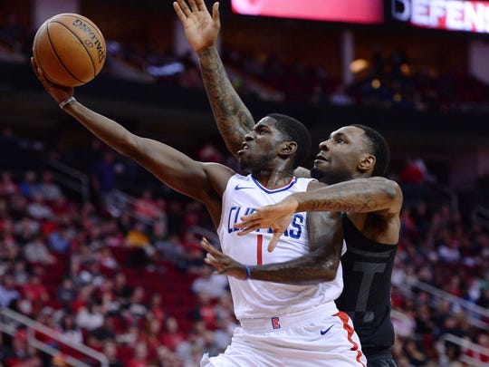 Houston Rockets forward Tarik Black, right, goes up to block the shot of Los Angeles Clippers Jawun Evans (1) during the first half of an NBA basketball game Friday, Dec. 22, 2017, in Houston. (AP Photo/George Bridges)