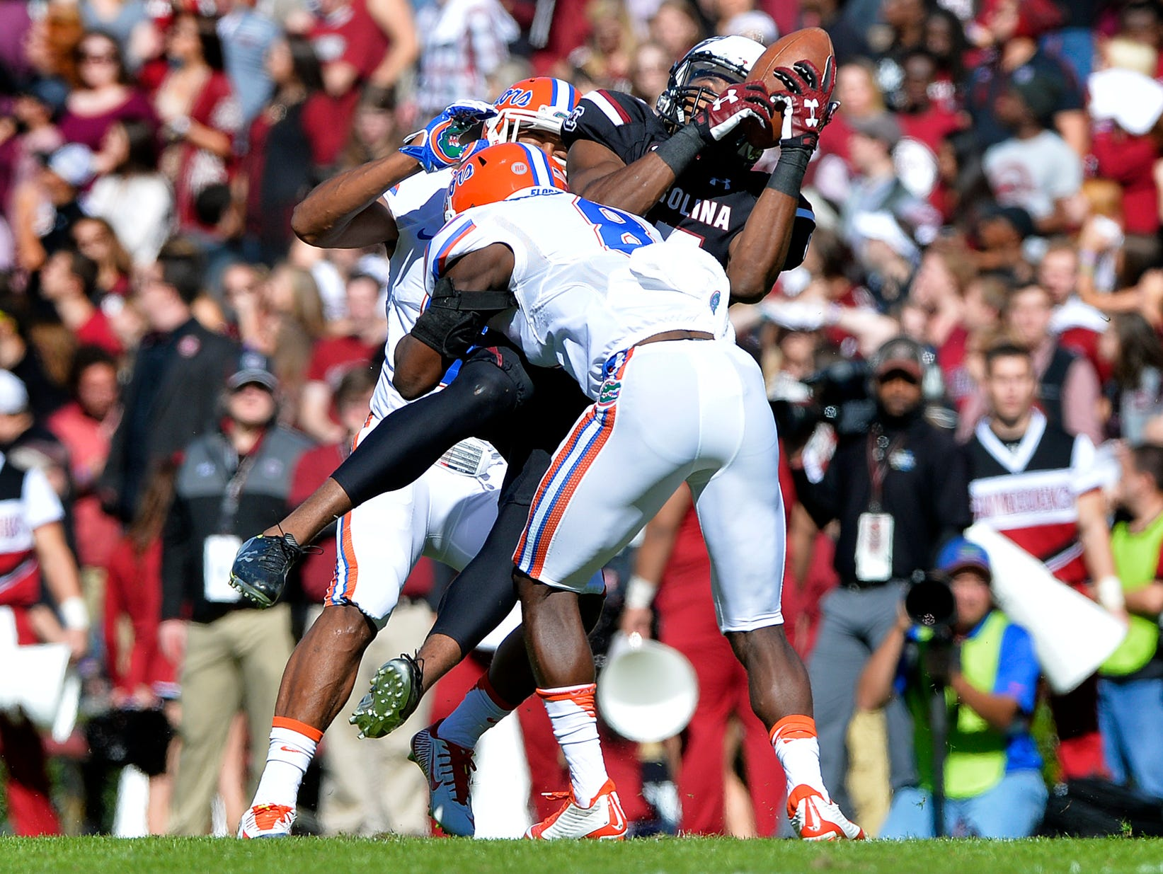 USC wide receiver Matrick Belton (15) makes a big catch but takes a big hit from two Florida defenders at Williams-Brice Stadium in Columbia on Nov. 14, 2015.
