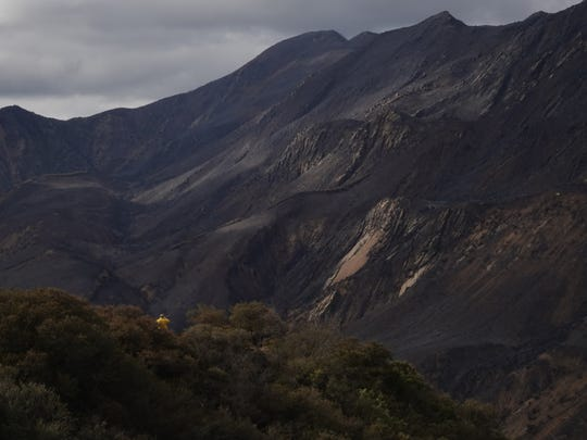 Steep canyon walls blackened by the Thomas Fire loom