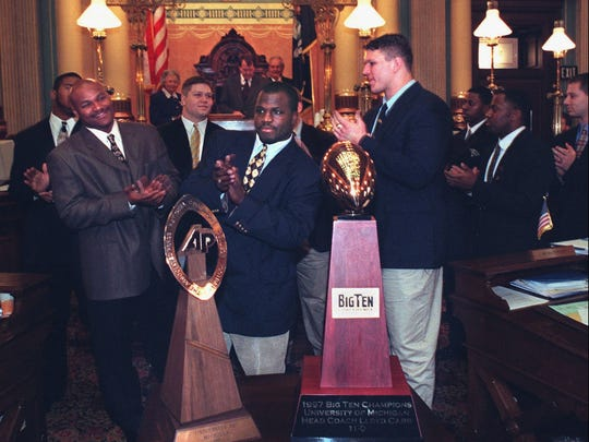 Michigan football team members Sam Sword, left, Eric Mayes, center, and Jon Jansen, right, applaud coach Lloyd Carr as the national championship Wolverines are honored in the state Senate chamber in Lansing on Feb. 12, 1998.
