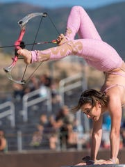 A contortionist fires a bow and arrow with her feet during The Garden Bros Circus in the Iron Ranger's Arena in Cedar City Tuesday, June 26, 2018.