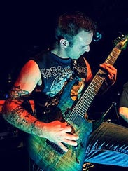 Nick Uchiha of MyNorth playing rhythm guitar at a live