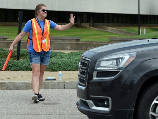 University of Southern Indiana resident assistant Erin Bonner of McLeansboro, Ill., waves to students and parents while directing traffic along University Blvd., as they make their way to residence halls to unload items during Welcome Week on campus Thursday.