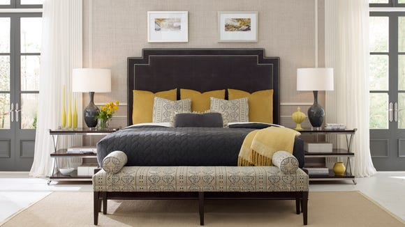 This stately bedroom displayed at High Point features a king size bed with a tall, custom made upholstered headboard.