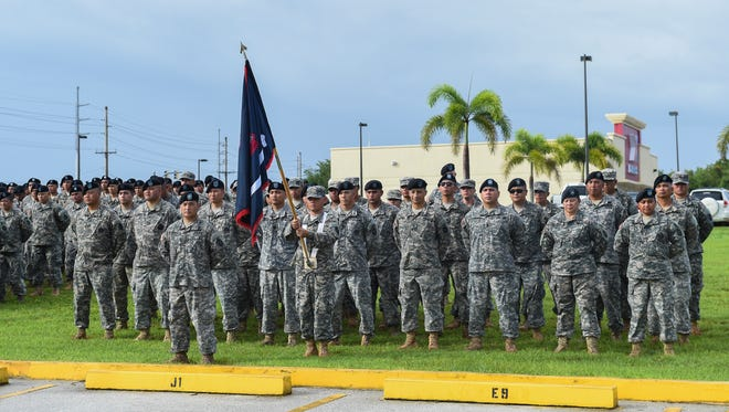 Guam National Guard soldiers and airmen stand at attention during the Guam National Guard Retreat Ceremony at the National Guard Readiness Center in Barrigada on Aug. 7, 2015.