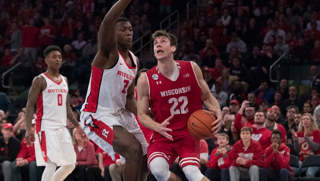 Wisconsin forward Ethan Happ (22) drives to the basket past Rutgers guard Corey Sanders (3) and guard Nigel Johnson (0) during overtime Saturday at Madison Square Garden in New York. Wisconsin won 61-54.