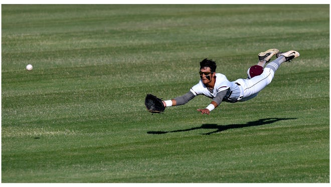 Hawley center fielder Garrett Hewitt dives for a low-flying ball but falls short of the catch during Thursday's game against New Deal. Hawley lost 10-1.