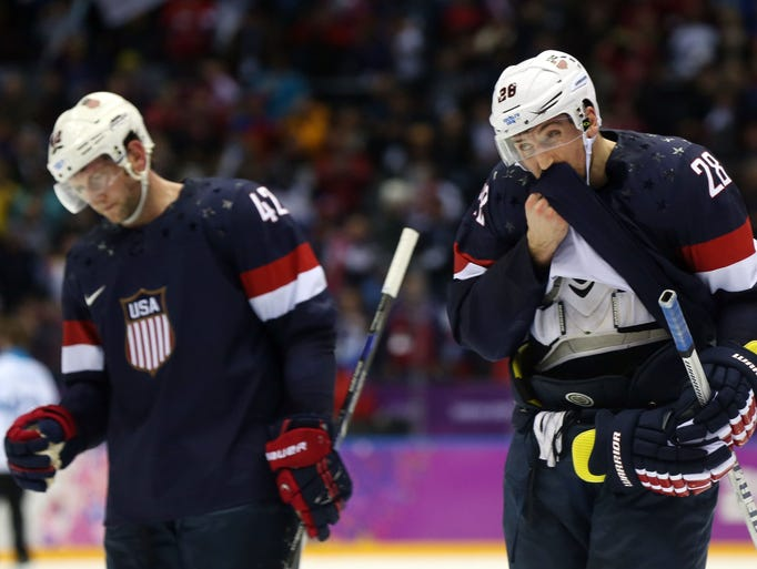 USA forward Blake Wheeler (28) and forward David Backes (42) skate off the ice after losing to Finland.