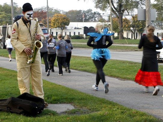 Runners pass a costumed saxophonist at the 5k/10k split