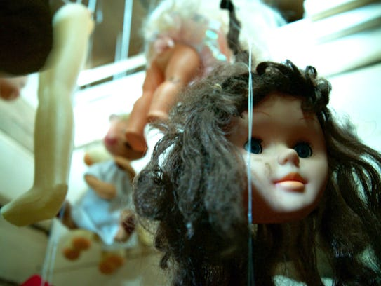 A few doll body parts strung from the ceiling.