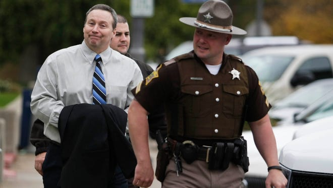David Camm reacts as he is led away from the Boone County Courthouse by sheriff deputies after the jury begin deliberations in Camm's third trial in Lebanon, Ind. Camm is on his third trial for the murders of his wife Kim Camm, daughter Jill and son Bradley in 2000. His first two convictions were overturned on appeal.  Oct. 22, 2013
