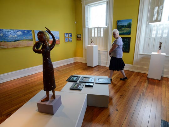 Cathy Kessler walks through one of the galleries Monday at the Decorative Arts Center of Ohio in downtown Lancaster. Kessler and docents were at the gallery for a walk-through of a new show displaying the work of local artists James Mason and Karen Rumora.