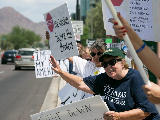 Judy Lairmore waves to passing cars during a protest outside of Senator McCain's Phoenix office. Protesters were calling on the senator to increase border security.