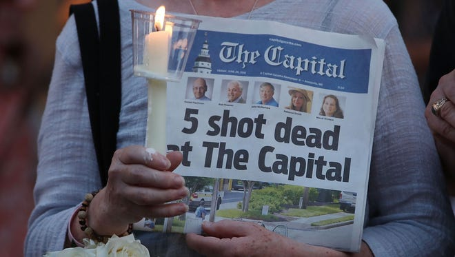 A women holds the June 29, 2018 edition of the Capital Gazette newpaper during a candlelight vigil on June 29 to honor the 5 people who were shot and killed the day before in Annapolis, Maryland.  Jarrod Ramos of Laurel Md. Has been arrested and charged with killing 5 people at the daily newspaper.