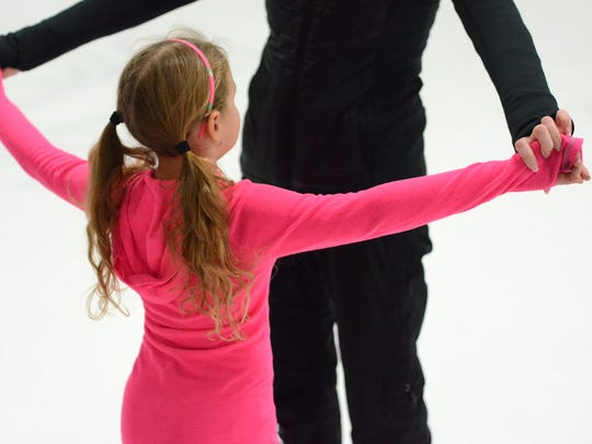 A skater is taught the proper way to stretch her arms