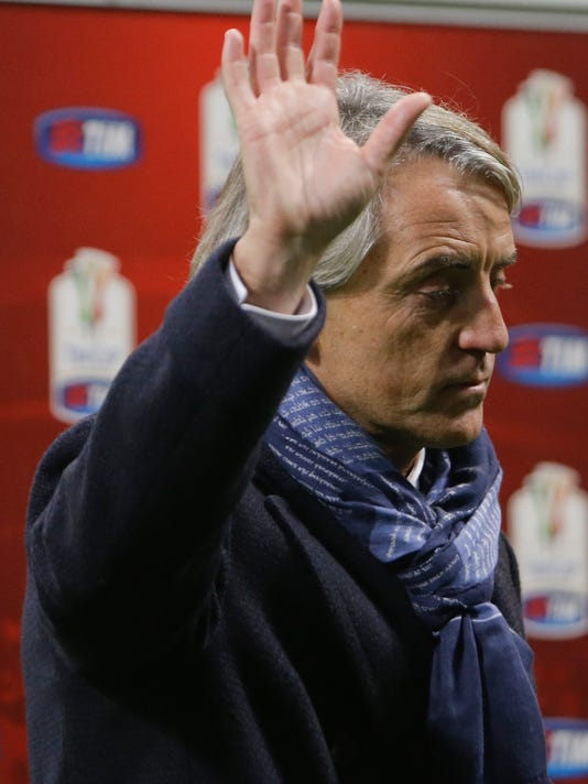 Inter Milan coach Roberto Mancini  waves to supporters at the end of a Serie A soccer match between Inter Milan and Genoa, at the San Siro stadium in Milan, Italy, Saturday, Dec. 5, 2015. Inter won 1-0. (AP Photo/Luca Bruno)