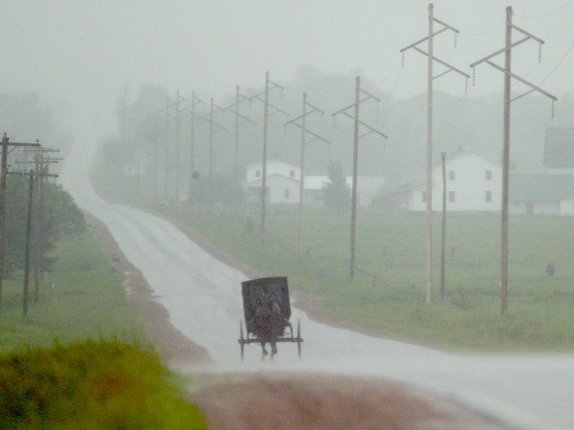 An Amish buggy drives through the rain in Clark County.